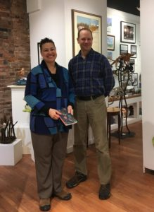 Dawn Ellis holds journal and stands by former Executive Director of Frog Hollow, Rob Hunter in the downtown Burlington, Vermont gallery.