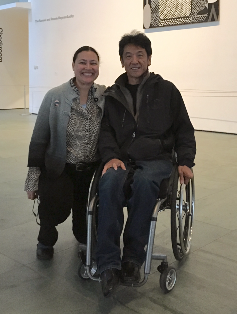 Photograph of Dawn Ellis kneeling next to Gordon Sasaki sitting, one hand on leg other on his wheel, at the Museum of Modern Art in NYC. Both smiling.
