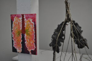 Black lung scuplture hangs next to pink lung painting