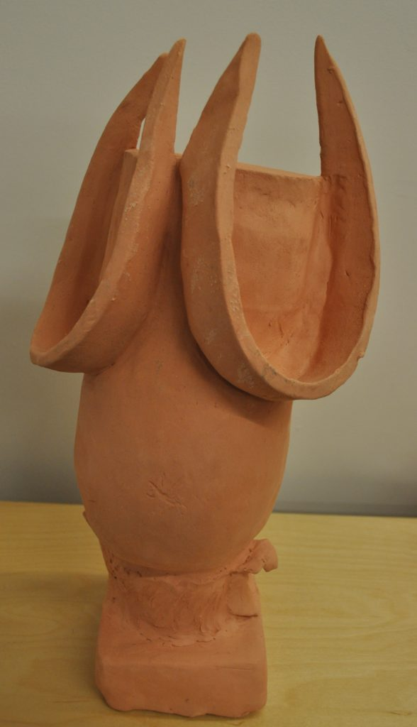Rough textured bisque fired handbuilt vessel. Rounded belly pinch pot with slab slices suggesting the beginnings of breasts, empty, sits on pedestal.